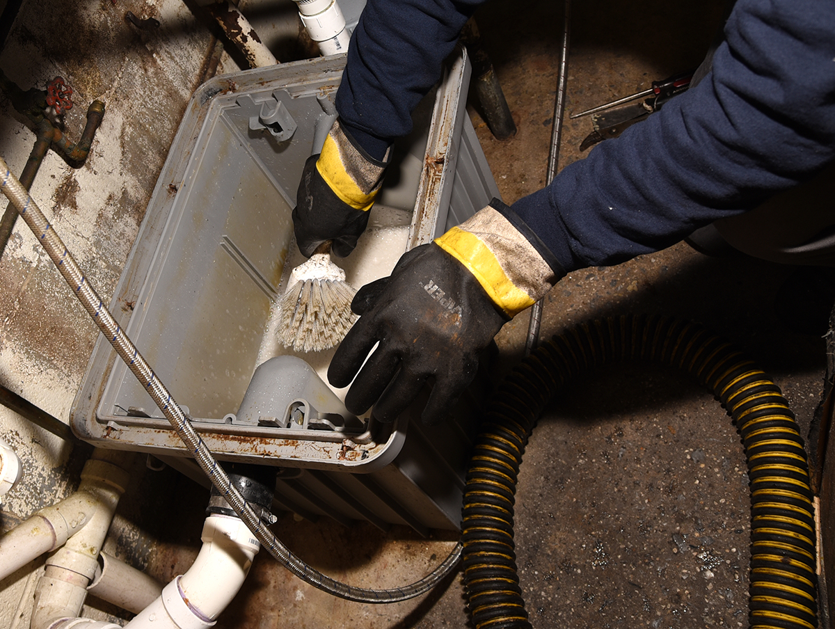 Man cleaning grease trap.