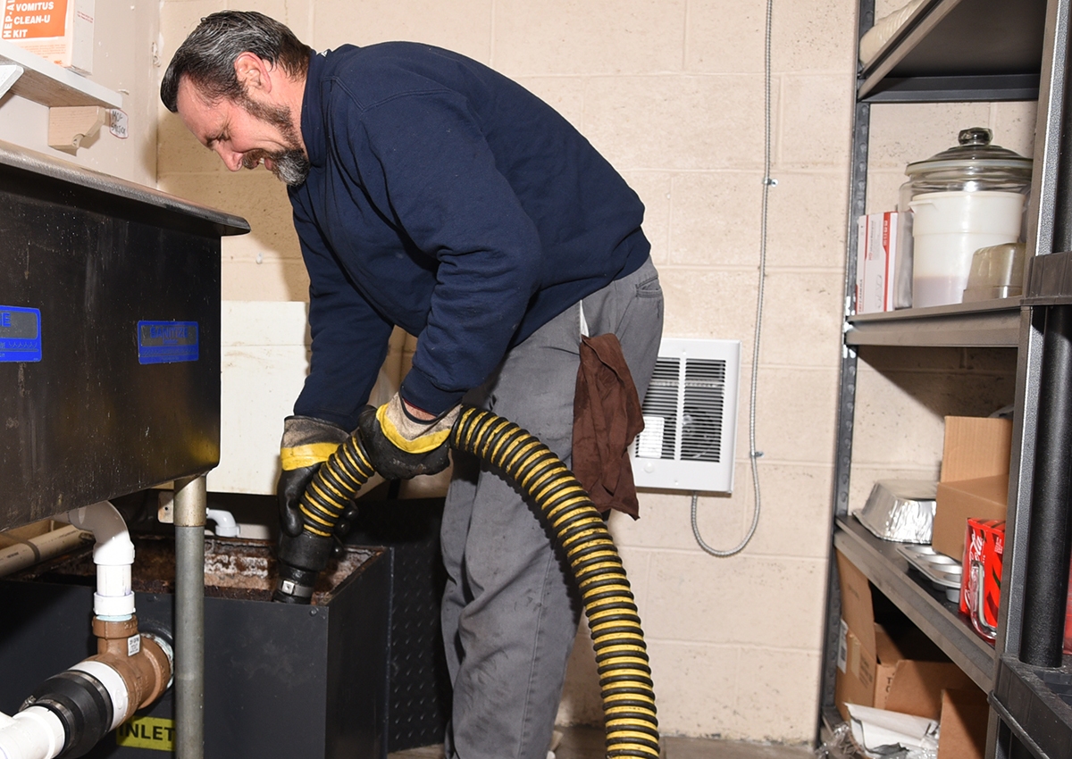Man inserting pipe in grease trap.